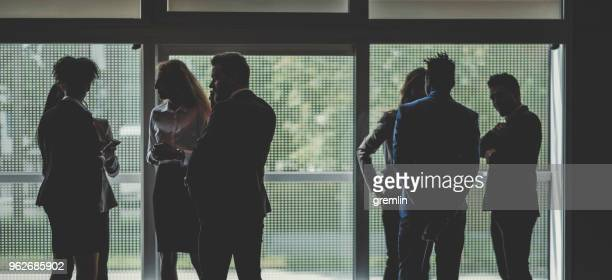 silhouette of standing business people in the office - local politics stock pictures, royalty-free photos & images
