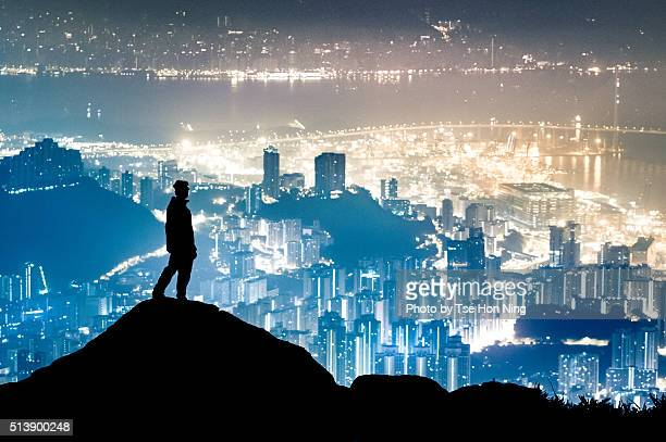 silhouette of standing hiker with hong kong city urban night view