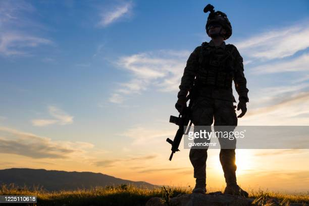 silhouette of standing soldier in battlefield at sunset - special forces stock pictures, royalty-free photos & images