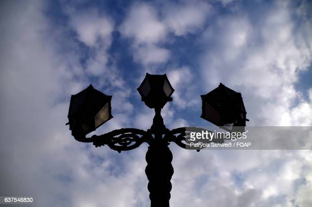 Silhouette of street light against cloudy sky