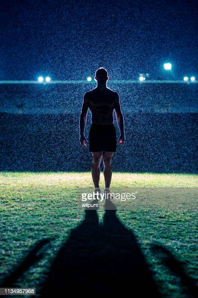 silhouette of strong male athlete standing in front of stadium in the rain at night - famous footballers silhouette stock pictures, royalty-free photos & images