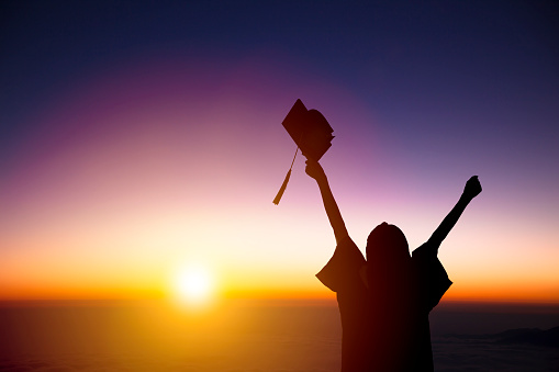 silhouette of Student Celebrating Graduation watching the sunlight 683527292