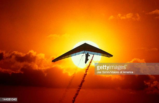 Silhouette of stunt hang glider in the sunset