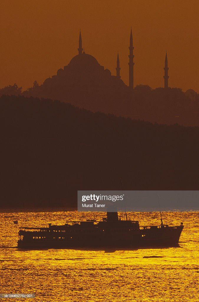 Silhouette of Suleymaniye Mosque and passanger ferry at sunset : Foto stock