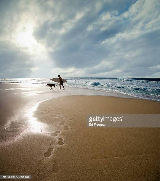 Silhouette of surfer with dog walking on beach