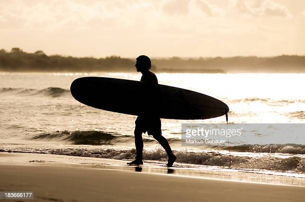 Silhouette of surfer with his board on the beach at down.