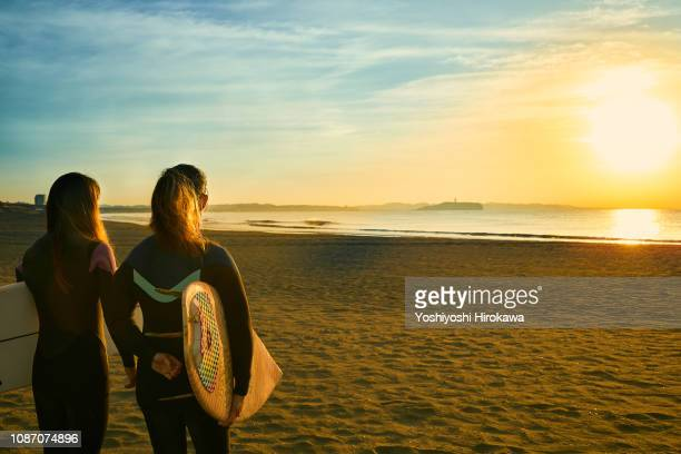 silhouette of surfer women standing on beach with surfboard in the morning glow coast. - obscured face stock pictures, royalty-free photos & images