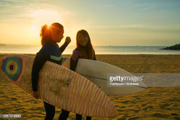 Silhouette of surfer women standing on beach with surfboard in the morning glow coast.