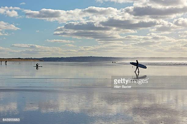 silhouette of surfers across saunton sands - sand stock pictures, royalty-free photos & images