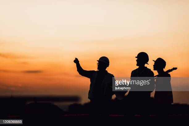 silhouette of survey engineer and construction team working at site - crash site stock pictures, royalty-free photos & images
