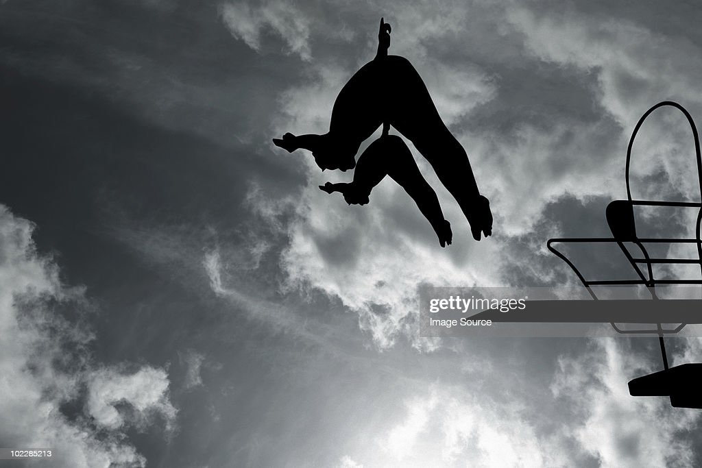 Silhouette of swimmers diving : Stock Photo
