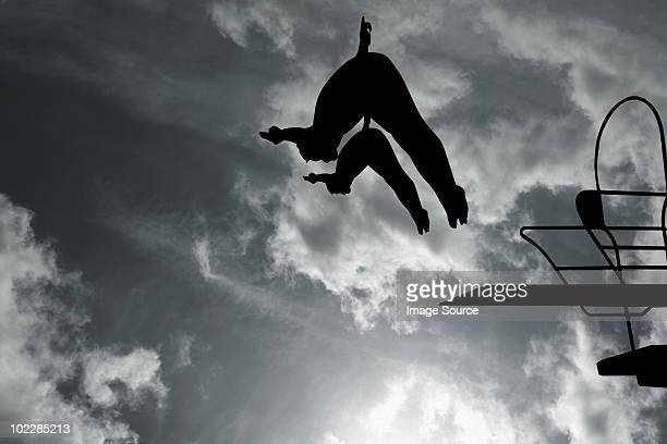 Silhouette of swimmers diving