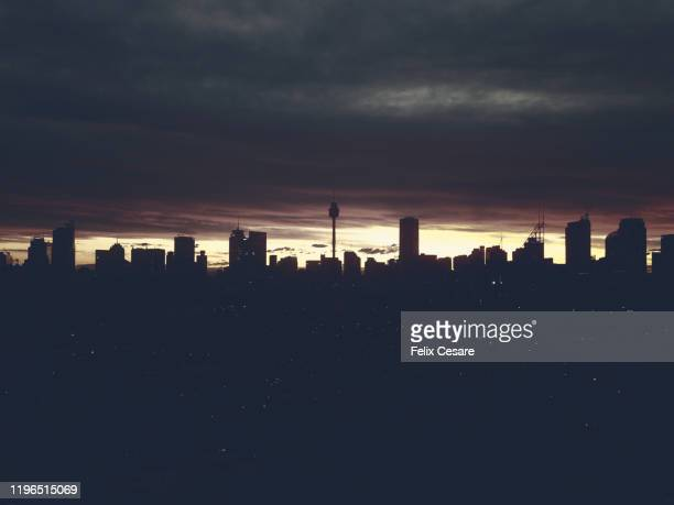 a silhouette of sydney cbd skyline cityscape against cloudy sky - sydney stock pictures, royalty-free photos & images
