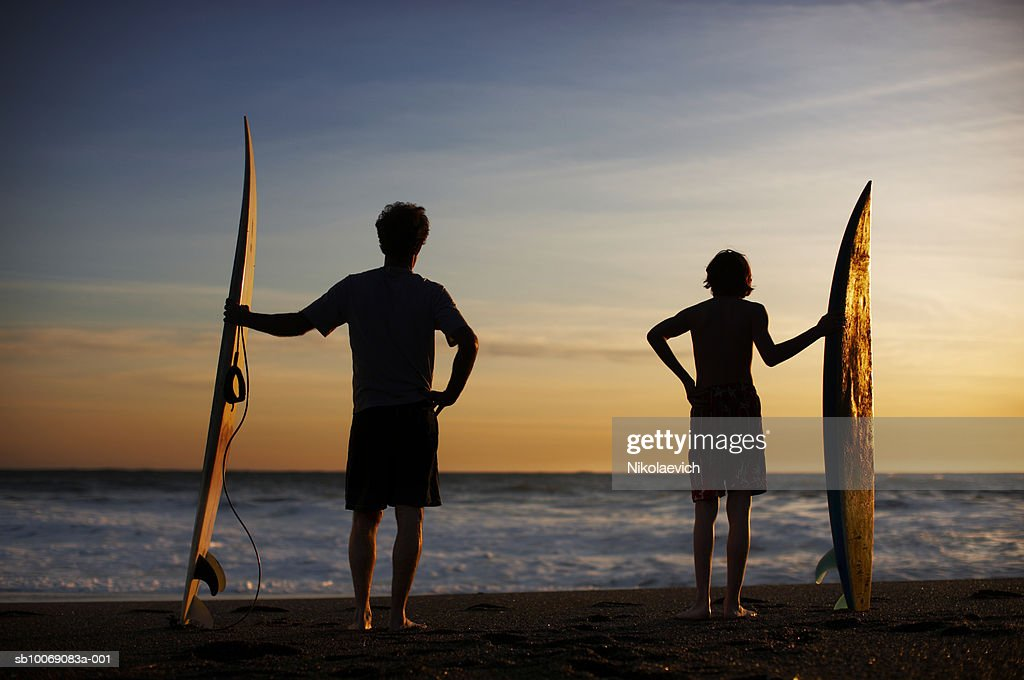 Silhouette of teenage boy (14-15) and father with surfboards on beach, rare view : Stockfoto