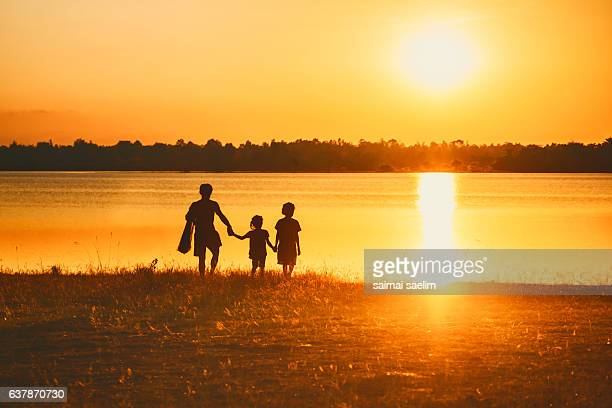 Silhouette of Thai fisherman family, sunset time, Thailand