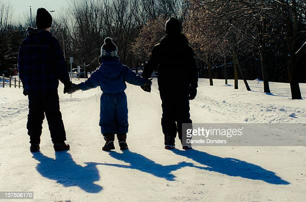 Silhouette of three brothers holding hands