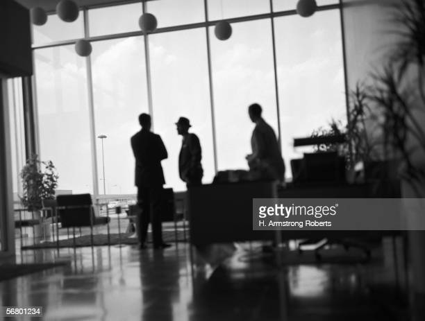 Silhouette of three businessmen meeting in lobby