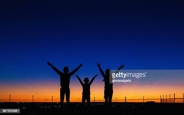 Silhouette of three children with arms in the air at Sunset, Kalgoorlie, Australia