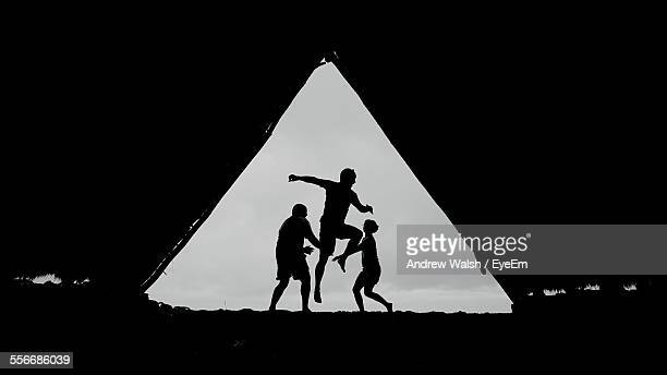 Silhouette Of Three Men Playing