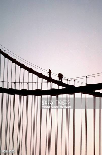 Silhouette of three people walking on Bay Bridge, San Francisco, California, USA