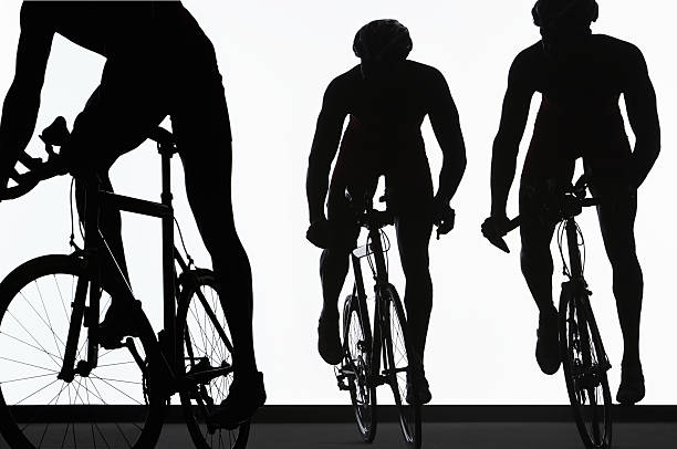 Silhouette of three triathletes riding on bicycles