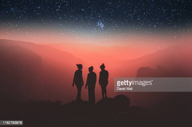 a silhouette of three woman silhouetted against a glowing red mountain landscape. with stars in the night sky above. - fantasy stock pictures, royalty-free photos & images