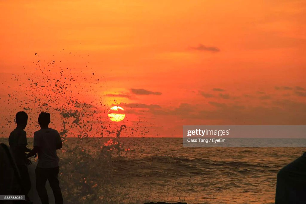 Silhouette Of Tourists Standing On Beach : Foto stock