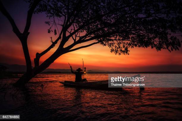 Silhouette of traditional fishermen fishing at sunrise time