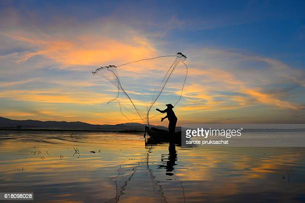 Silhouette of traditional fishermen throwing net fishing at sunrise time.