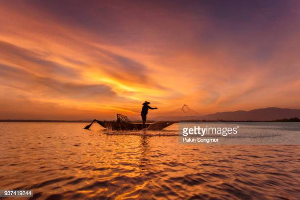 Silhouette of traditional fishermen throwing net fishing inle lake at sunrise time, Myanmar