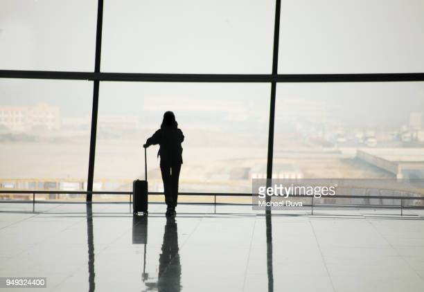 silhouette of travelers in airport - passenger stock pictures, royalty-free photos & images