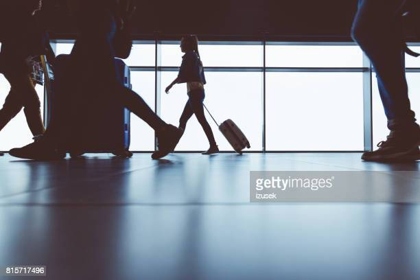 Silhouette of travelers with luggage walking at airport