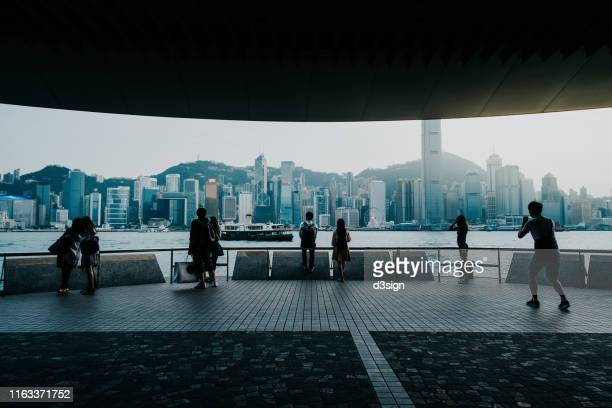 silhouette of travellers enjoying the spectacular city skyline of hong kong by the promenade of victoria harbour - central stock pictures, royalty-free photos & images
