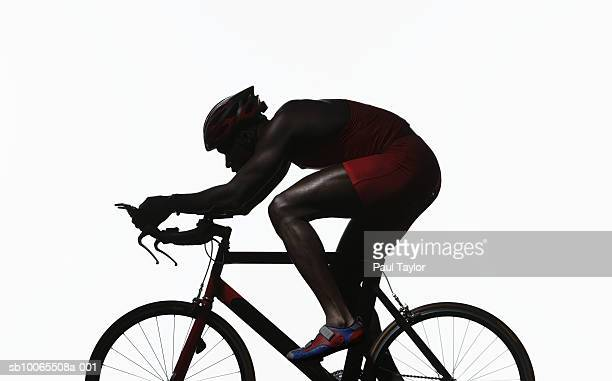 Silhouette of triathlete riding on bicycle, side view