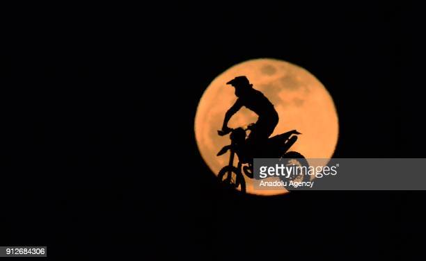 Silhouette of Turkish motocross champion Asrin Rodi Pak riding a motocross is seen in front of the 'Super blue blood moon' Motorcross Track of Usak...