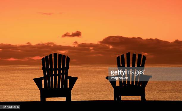 Silhouette of Two Adirondack Chairs on the Beach