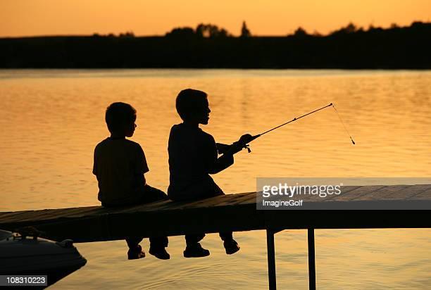 silhouette of two boys de un muelle de pesca - muelle dársena fotografías e imágenes de stock