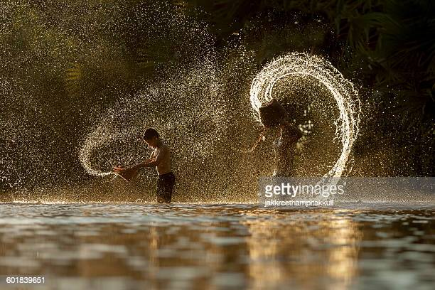 Silhouette of two boys splashing in the river, Thailand