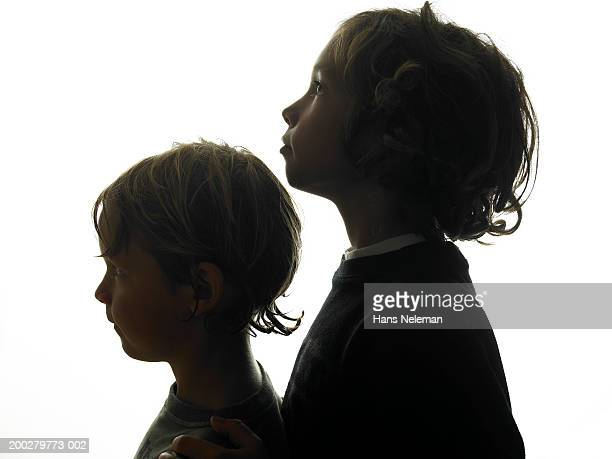 Silhouette of two boys (5-8) standing in line, side view, close-up