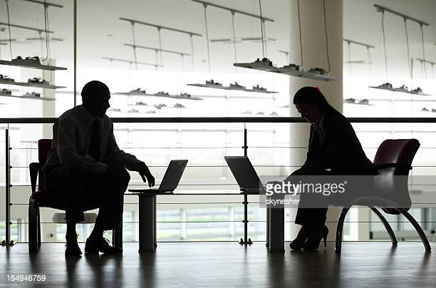 Silhouette of two business people at the workplace.