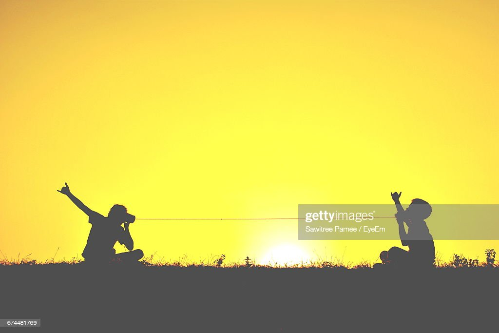 Silhouette Of Two Children With Tin Can Phones At Sunset : Stock Photo