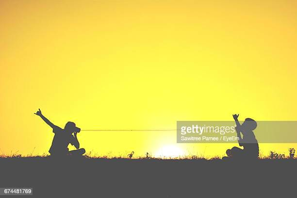 Silhouette Of Two Children With Tin Can Phones At Sunset