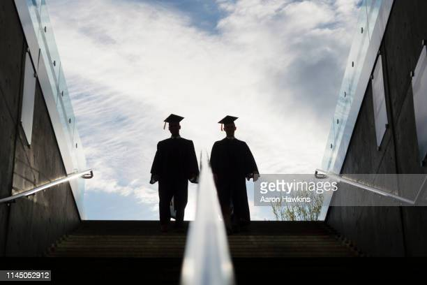 silhouette of two college graduates climbing steps - post secondary education stock pictures, royalty-free photos & images