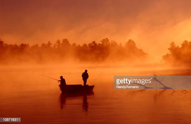 Silhouette of two fishermen on boat on a misty river
