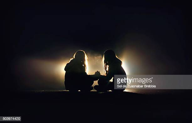 Silhouette of two girls sitting on the pavement of a road, facing, holding hands in the dark