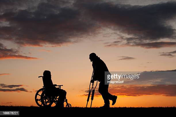 Silhouette of Two Injured People on Crutches and Wheelchair