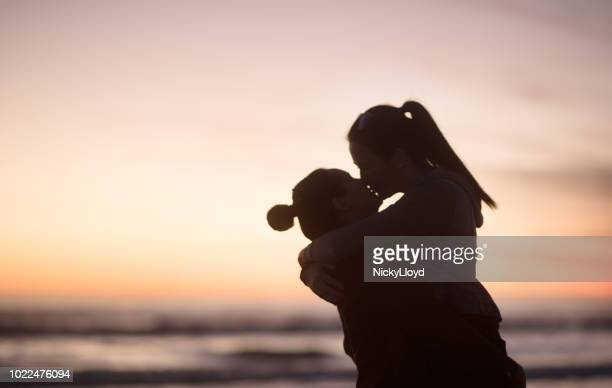 silhouette of two lovers standing face to face - lesbica bacio foto e immagini stock