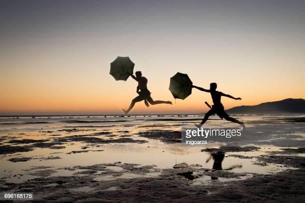 silhouette of two men holding umbrellas jumping, los lances beach, tarifa, cadiz, andalucia, spain - tarifa stock photos and pictures