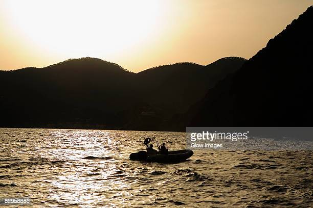 Silhouette of two people in an inflatable raft, Italian Riviera, Mar Ligure, Genoa, Liguria, Italy