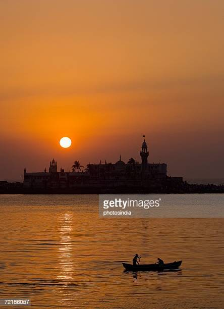 Silhouette of two people on a boat in the sea with a mosque in the background, Haji Ali Dargah, Mumbai, Maharashtra, India